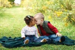 Enfants en bas âge interraciaux montrant l'affection Racisme de combat Images stock
