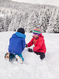 Enfants en bas âge jouant dans la neige Photos libres de droits