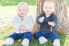 Enfants en bas âge jumeaux s'asseyant près du tronc d'arbre Photos libres de droits