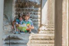 Enfants en bas âge regardant la carte de touristes dans Angkor Vat, cambodi Image stock
