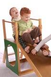 Enfants en bas âge sur la glissière de cour de jeu Photographie stock
