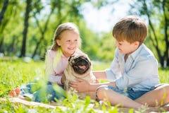Enfants en parc avec l'animal familier Photo libre de droits