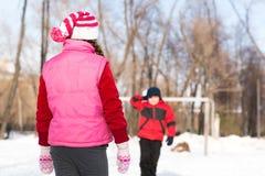Enfants en parc d'hiver jouant des boules de neige Photos stock