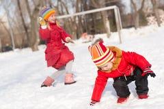 Enfants en parc d'hiver jouant des boules de neige Image stock