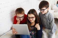 Enfants en verres avec des instruments, dépendance d'ordinateur Photographie stock