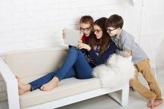 Enfants en verres avec le comprimé, dépendance d'ordinateur Photographie stock libre de droits