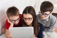Enfants en verres avec le comprimé, dépendance d'ordinateur Photos stock