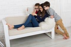 Enfants en verres avec le comprimé, dépendance d'ordinateur Photographie stock