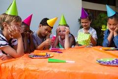 Enfants ennuyés pendant la fête d'anniversaire images stock