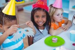 Enfants enthousiastes appréciant une fête d'anniversaire Photos stock