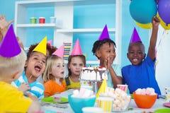 Enfants enthousiastes appréciant une fête d'anniversaire Photo stock