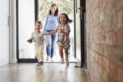 Enfants enthousiastes arrivant à la maison avec des parents image libre de droits