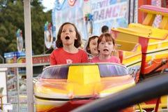 Enfants enthousiastes criant sur le tour de montagnes russes de carnaval photo libre de droits
