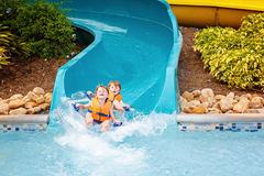 Enfants enthousiastes dans l'équitation de parc aquatique sur la glissière avec le flotteur Photographie stock