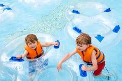 Enfants enthousiastes dans l'équitation de parc aquatique sur la glissière avec le flotteur Image libre de droits