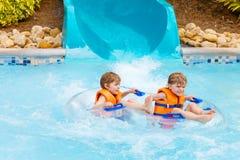 Enfants enthousiastes dans l'équitation de parc aquatique sur la glissière avec le flotteur Photos stock