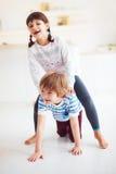 Enfants enthousiastes heureux ayant l'amusement, montant sur le dos à la maison Image stock