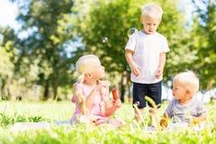 Enfants enthousiastes jouant tous ensemble en parc images stock