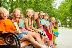Enfants enthousiastes s'asseyant sur le banc dans une rangée Image libre de droits