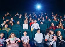 Enfants et ados observant la bande dessinée dans le cinéma et exprimant différentes émotions photographie stock