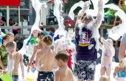 Enfants et adultes jouant dans les bulles à une rue juste Photos libres de droits
