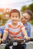 Enfants et bicyclette asiatiques d'équitation d'émotion de bonheur de mère dans le village à la maison images libres de droits
