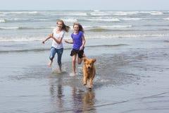 Enfants et chien fonctionnant à la plage Photographie stock libre de droits
