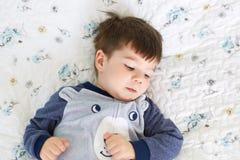 Enfants et concept de relaxation Le petit enfant masculin avec le regard adorable, mensonges sur le lit confortable, regarde pens photo stock