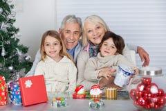 Enfants et grands-parents avec des cadeaux de Noël images stock