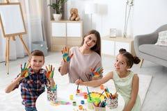 Enfants et jeune femme mignons avec les mains peintes à la table photo stock