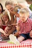 Enfants et mères à la réception de thé extérieure Photos stock