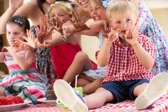 Enfants et mères mangeant le gâteau à l'extérieur Photos libres de droits