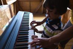Enfants et mains des femmes sur les clés de piano image stock
