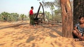 Enfants et moulin primitif pour serrer l'huile de palme banque de vidéos