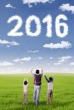 Enfants et papa heureux avec les numéros 2016 au champ Photos stock