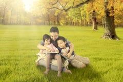 Enfants et papa lisant un livre au parc d'automne Photographie stock libre de droits