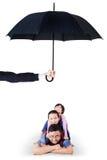 Enfants et papa se situant dans le studio sous le parapluie Image stock