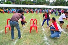 Enfants et parents faisant un travail d'équipe emballant au jour de sport de jardin d'enfants Photo stock