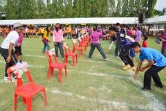 Enfants et parents faisant un travail d'équipe emballant au jour de sport de jardin d'enfants Photographie stock libre de droits
