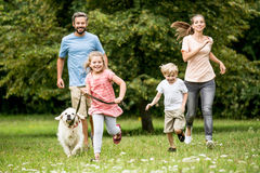 Enfants et parents heureux avec le chien Image stock