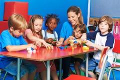Enfants et professeur de crèche jouant avec les blocs constitutifs Image libre de droits