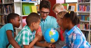 Enfants et professeur regardant le globe dans la bibliothèque clips vidéos
