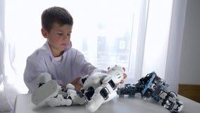Enfants et technologie moderne, jouet intelligent de robot de réparations de garçon avec l'intelligence artificielle dans le stud banque de vidéos