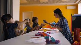 Enfants ethniques multi créant l'origami à la leçon de métier clips vidéos