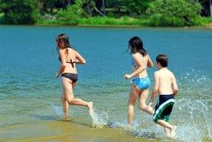 Enfants exécutant dans l'eau Photographie stock