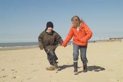 Enfants exécutant sur la plage Image stock