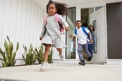Enfants excités courant hors de l'école de Front Door On Way To observée par la mère photos stock