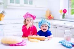 Enfants faisant cuire au four dans une cuisine blanche Image libre de droits