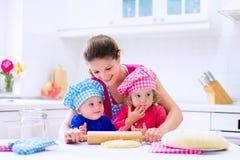Enfants faisant cuire au four dans une cuisine blanche Photos stock