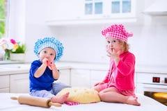 Enfants faisant cuire au four dans une cuisine blanche Photographie stock libre de droits